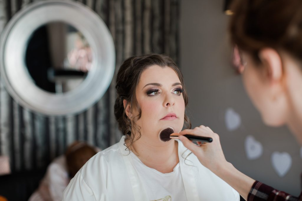 Bride having makeup done by makeup artist