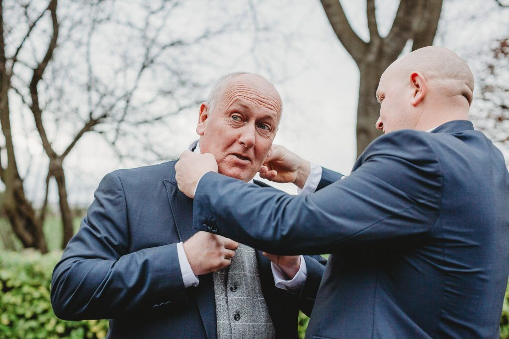 Groom helping father with final details