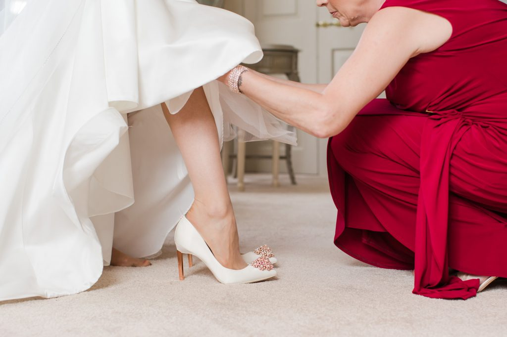 Mother of Bride helping put shoes on