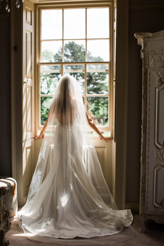Bride looking out the window watching guests arrive