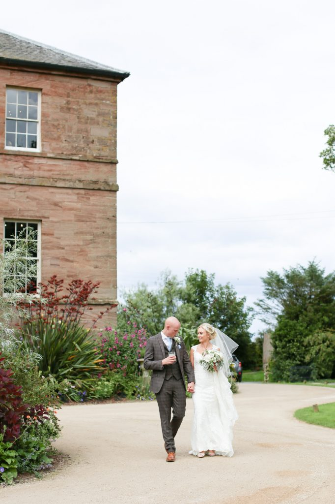 Bride and groom walk to meet guests