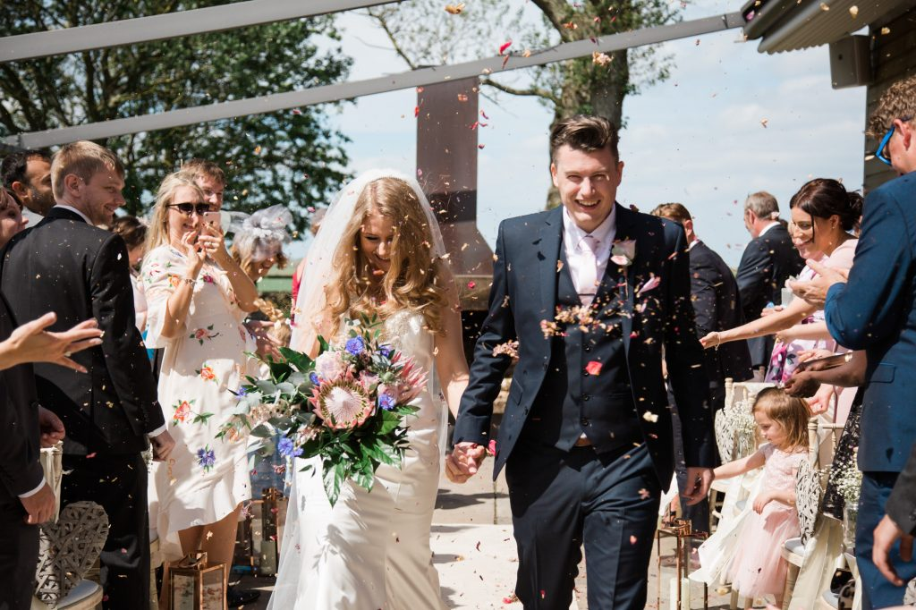 Bride and groom walk up Isle as guests throw confetti