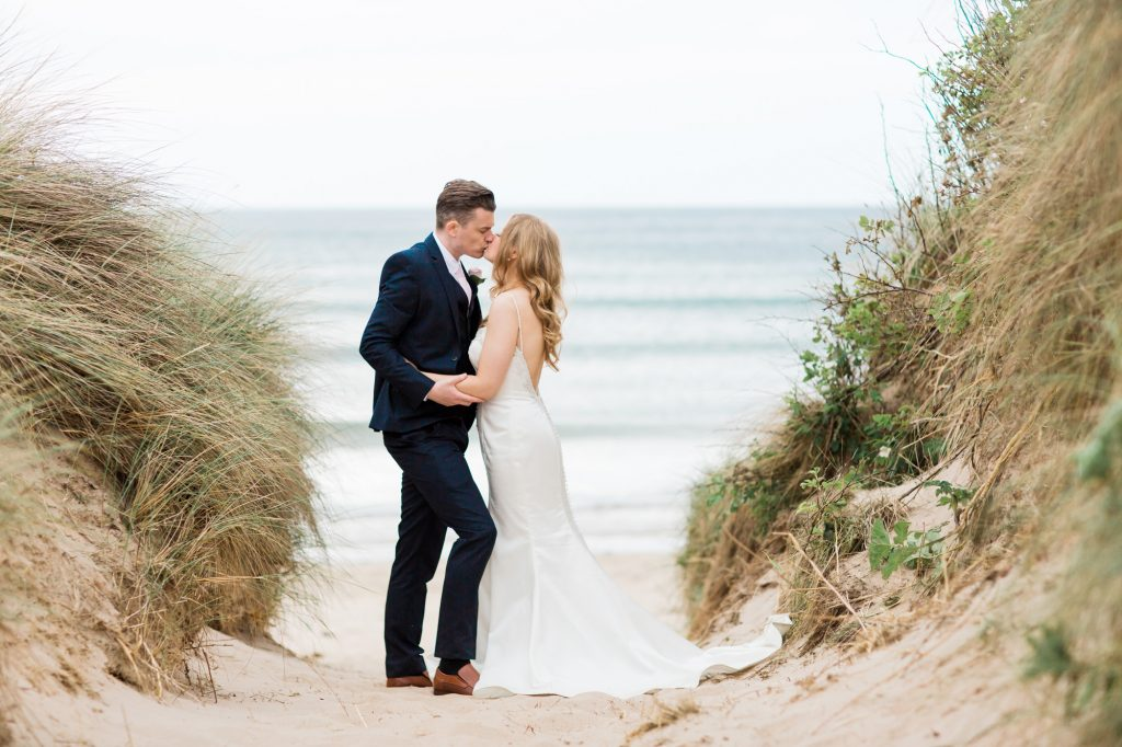 Bride and Groom kiss at beach