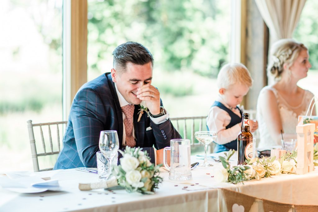 groom holds head in hands during speech