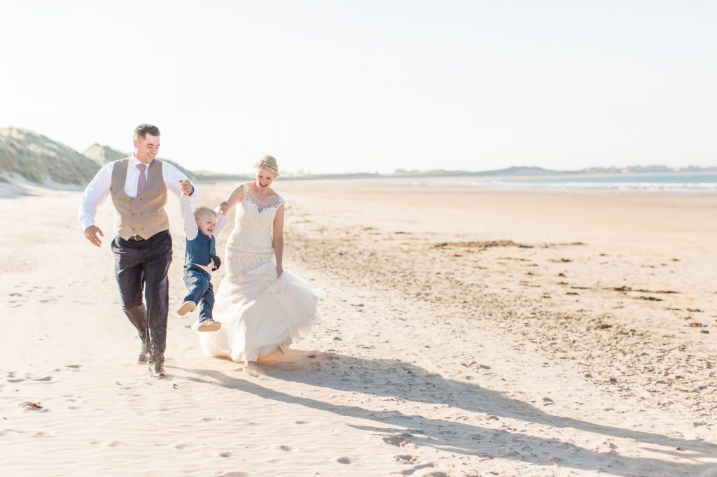 bride and groom swing page boy on beach